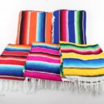 mexican serape blankets in orange, blue, red, pink and yellow with white fringe