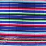 blue mexican serape blanket fully extended showing the complete striped design with various colors