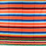 orange mexican serape blanket fully extended showing the complete striped design with various colors