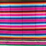 pink mexican serape blanket fully extended showing the complete striped design with various colors