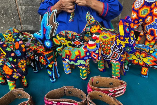 Mexican Huichol artist working on a variety of traditional beaded Mexican crafts